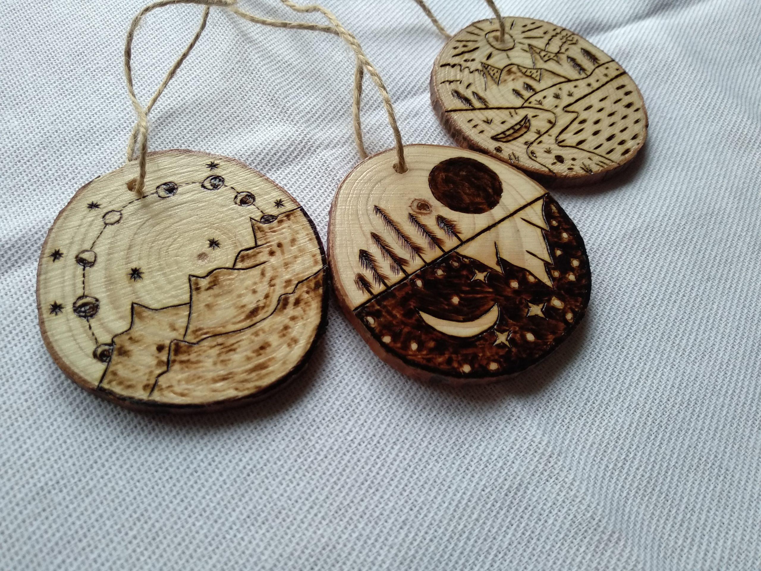 3 ornements en bois avec des montagnes et des lunes dessinés dessus